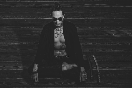 Reincarnation and rebirth. Man with tattooed torso sitting in meditation pose with swords