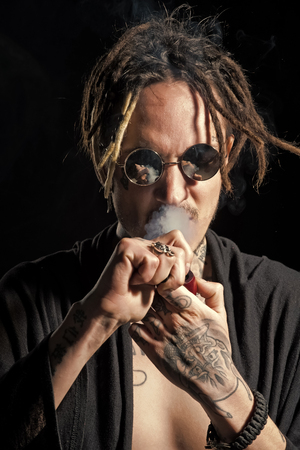 fashion portrait of a man. Hippy smoker with dreadlocks in sunglasses and bare chest Stock Photo