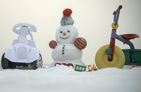 Snowman with smiley face on white sky. Tricycle, car and toys on snowy background