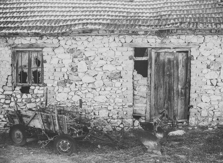 old abandoned barn. Abandoned cart next to ruins. Old cart near stone wall. District with old buildings, old building made of stones collapsing. The uninhabited house almost destroyed