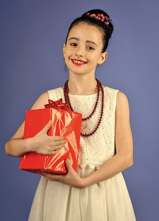 girl with a gift. Small girl with shopping package, black friday. Boxing day, holiday celebration and party. Child girl with present pack, cyber monday. Birthday and christmas. Childhood and happiness, gift box. Stock Photo