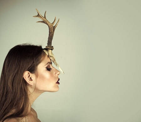 creative fashion photography. Woman with makeup and antlers. Fashion devil of mystic shaman girl with horns. Beauty look and cosmetics for skincare. Dark fantasy creature elf on halloween in skull. Chinese Horoscope and goat year Stock Photo