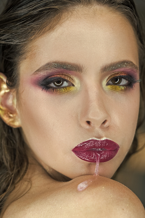 Fashion girl with bright makeup, beauty. Skincare, cosmetics and visage. Woman run saliva from mouth with purple lips, makeup. Woman with fresh skin face, skincare. Beauty model with glamour look