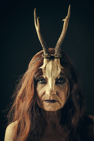 eldest woman with a creative make. Woman with makeup and antlers. Fashion devil of mystic shaman girl with horns. Beauty look and cosmetics for skincare. Dark fantasy