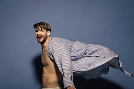 Happy bachelor with sexy torso in flying bathrobe Stock Photo