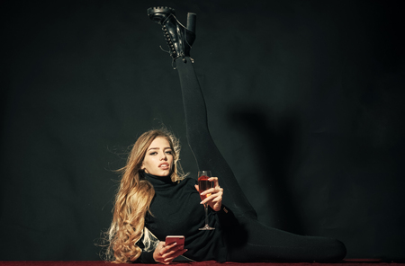 Fashion portrait. Hot sexy woman. Fashionable flexible lady with make up and skinny leg lay, black background. Girl with long hair raises leg, holds glass of wine and smartphone, copy space. Fashion and beauty concept 版權商用圖片