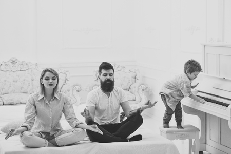 Mom and dad try to keep calm. Meditation concept. Young parents meditating, while their little son playing piano, annoying parents. Couple do yoga exercises in bed. Kid annoyed parents with noise