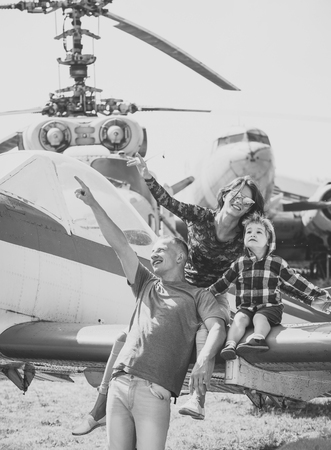 family in the aviation museum. Mother, father and excited child sit on planes wing in aviation museum. Happy family looking on sky on excursion, helicopter or plane on background, sunny day. Development and upbringing concept
