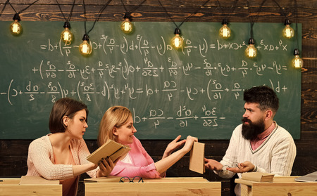 Students, young scientists studying, holds book , while professor teaches, explains, chalkboard background Girls students and bearded teacher, lecturer, professor. College and education concept.