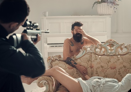 Cheating and jealousy concept. Husband found lovers, killed wife and threatening to bearded lover. Man with beard naked, disappointed at gunpoint, interior background. Man at gunpoint of killer. Stock fotó