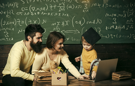 Parents teaches son, chalkboard on background. Modern education concept. Smart child in graduate cap likes to study. Parents teaching kid to use laptop. Boy presenting his knowledge to mom and dad 免版税图像