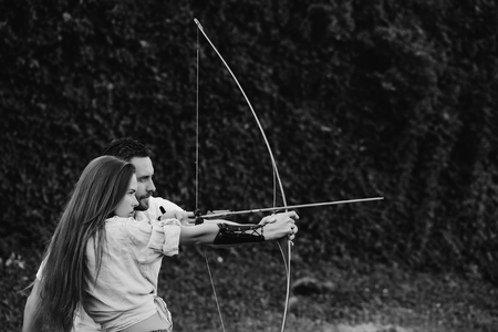 Concentrate and aiming. man and pretty woman shooting with bow and arrow Stockfoto - 103094208