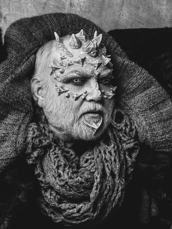 Man with dragon skin and beard. Monster face with white eyes, sharp thorns and warts