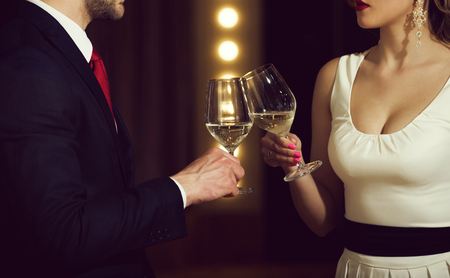 partnership. clink glasses with white wine of couple at meeting