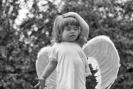 Cares of angels. small boy in angel wings