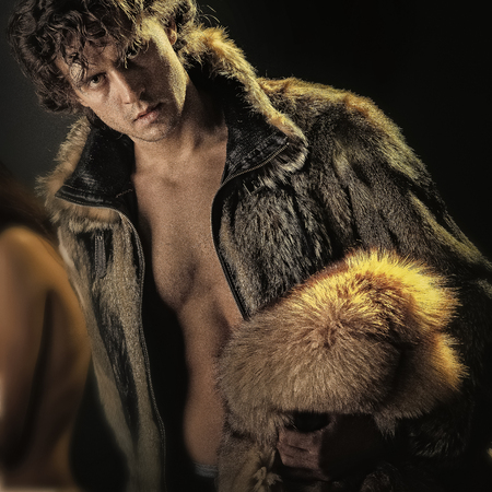 Glamour and luxury lifestyle concept. Man posing in open fur coat