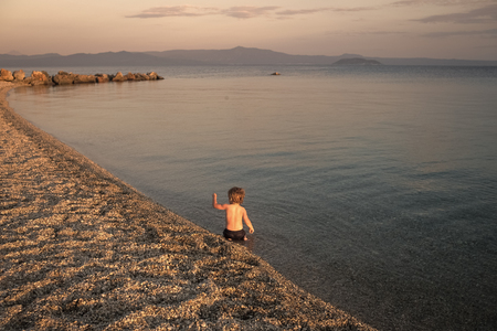 boy on the beach. concept of loneliness. Cute child waving hand at seashore in evening. Boy sits in sea water, rear view. Farewell and parting concept. Toddler on vacation farewells with summer holidays on sunset. Summertime sadness.