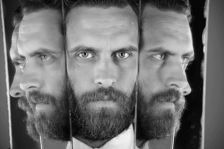 split personality. face of serious bearded hipster man, businessman reflecting in mirror