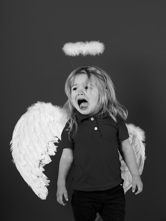 Angels also cry. little angel boy crying with white feather wings and halo