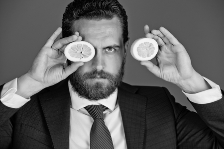 healthy food and dieting. man with beard or businessman holding yellow fruit, lemon