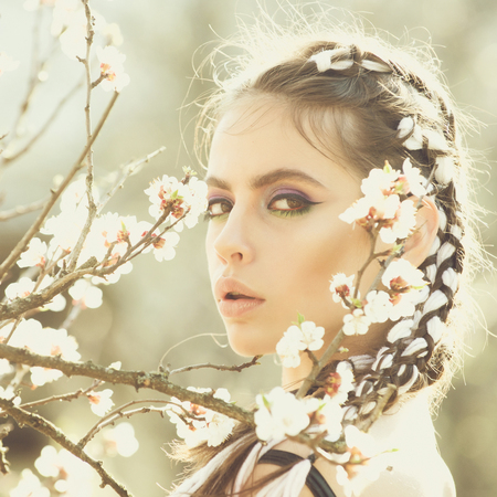 Skin care and beauty. beautiful girl in spring park with flowers