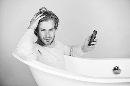 Selfi in the bathroom. handsome young man in bathtub with mobile phone Stock Photo