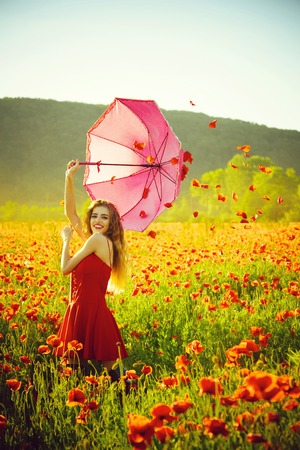 umbrella sale. woman in field of poppy seed with umbrella
