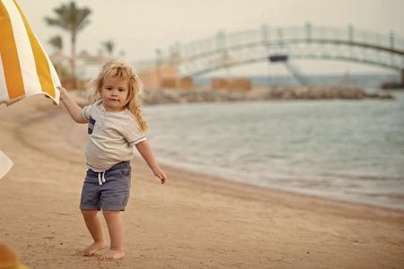 childrens leisure. Boy little child holding striped white and yellow towel Standard-Bild - 103130029