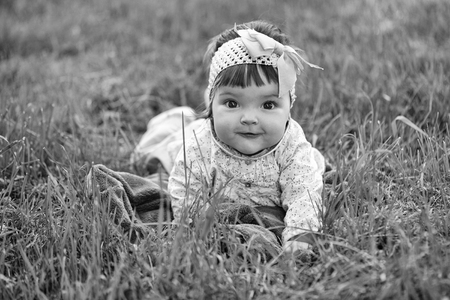 child lies on the grass and smiles. Cute baby girl on green grass Banco de Imagens