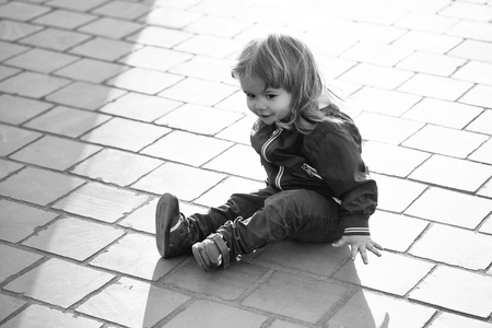 child is sitting on the asphalt. Little boy sits on pavement