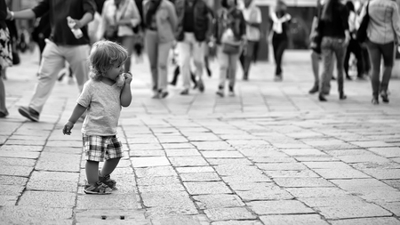 boy in the middle of the square with people. Baby boy eating bun Stock Photo