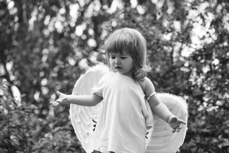 angel reflects on the fate of people. small boy in angel wings