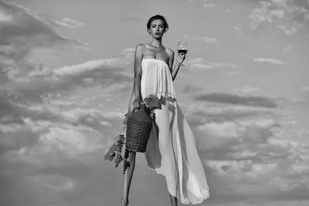 advertising wine. pretty girl with wine bottle over sky