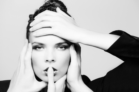 high fashion portrait. manicured hands on cute face of adorable woman