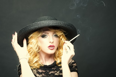 lady in years smokes a cigarette. Smoking retro woman Foto de archivo