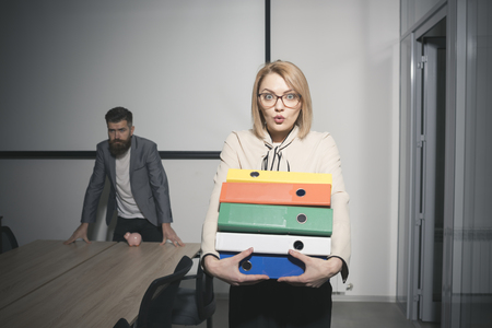 Surprised woman and bearded man on background. Business woman in glasses hold file folders. Sexy secretary with office documents. Paperwork and bureaucracy concept. Busy day in office
