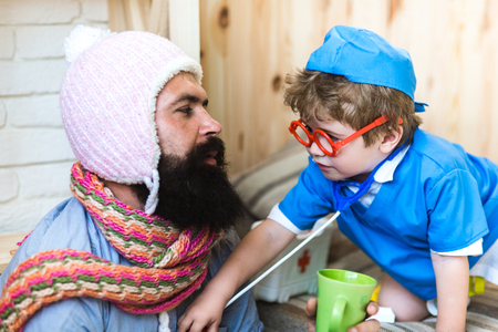 Consulting on the go. Son in glasses with stethoscope examine father at home. Little child play doctor with man. Medicine and health. Boy in doctor uniform treat patient. Game and development