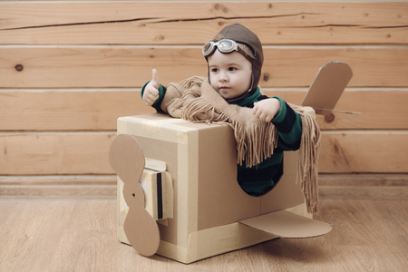cardboard plane with childhood, little boy pilot.