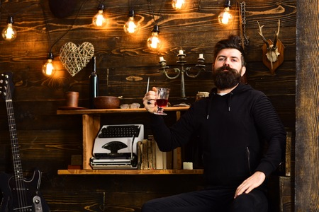 Relaxing evening. Guy in cozy warm atmosphere drinking. Man bearded enjoy evening with warming beverage, wooden background. Man with beard holds glass of mulled wine hot seasonal beverage