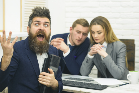 Business partners or businessman at meeting, office background. Startup concept. Business negotiations, discuss conditions of deal. Man with beard and folder proposes extraordinary crazy startup idea
