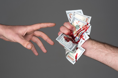 Hand injured bloody finger holds dollar banknote grey background. Dirty money concept. Bloody currency. Handover criminal profit. Dollar marked by murder. Money covered with traces of crime