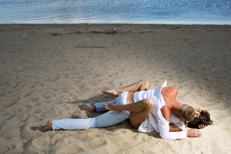 Family and valentines day. Summer holidays and paradise travel vacation. Sexy woman and man have sex games. Couple in love with sexy body relax on beach sand. Love relations of naked couple at sea. Stock Photo