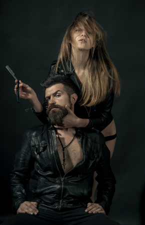 Barber concept. Couple of sexy girl and brutal bearded hipster with mustache, black background. Hipster with beard and sexy girl holds straight razor. Barber with straight razor works on haircut Stock Photo