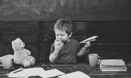 break between classes. Kid eating apple with pleasure. Cute boy biting fruit with his eyes closed. Infant playing with paper plane