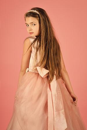 Fashion and beauty, little princess. Fashion model on pink background, beauty. Little girl in fashionable dress, prom. Look, hairdresser, makeup. Child girl in stylish glamour dress, elegance Stock Photo