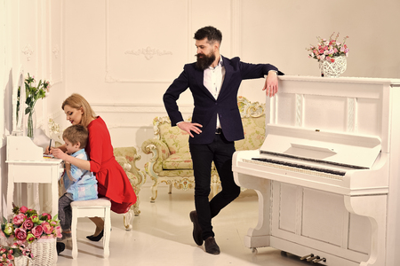 joy of parenting. Home schooling concept. Father stands near piano, watching while mother teaches son preschooler to draw or write, luxury interior. Kid growthing in welfare. Parents enjoying parenthood, happy