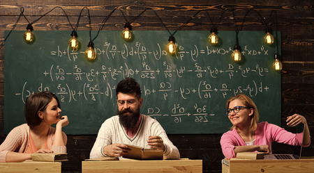 Students, young scientists . Girls, happy students looking with adoration at bearded teacher, lecturer, professor. College and education concept. Students, young scientists fall in love with professor chalkboard background. Stock Photo