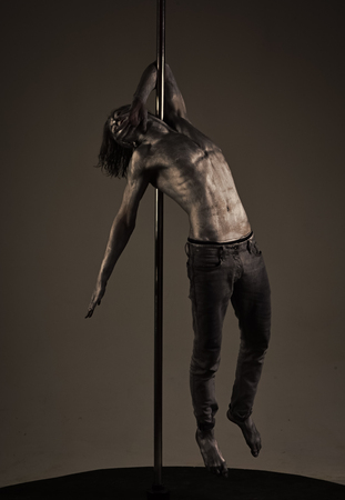 living statue. Guy hanging on metallis pole. Performance concept.