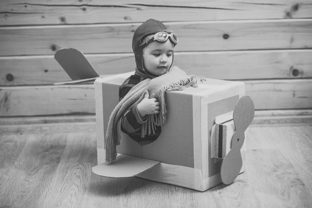 Childhood. Fantasy, imagination. Brave dreamer boy playing with a cardboard airplane Stockfoto