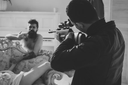 contract killing. Cheating and jealousy concept. Husband found lovers, killed wife and threatening to bearded lover. Man with beard naked, pray for mercy at gunpoint, interior background.